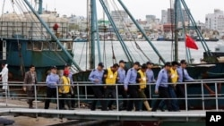 Chinese fishermen, wearing yellow jackets, are led by South Korean police officers after they were arrested at a port in Mokpo, South Korea, Wednesday, Oct. 17, 2012. The South Korean coast guard on Tuesday fatally shot a Chinese fisherman with a rubber b
