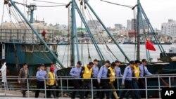 Seorang nelayan China (berpakaian kuning) dikawal ketat oleh polisi Korea Selatan di pelabuhan Mokpo, Korea Selatan (Foto: dok). Kapten sebuah kapal ikan China terbunuh hari Jumat (10/10), setelah berselisih dengan para petugas pengawal pantai Korea Selatan, yang mencegat kapalnya karena dicurigai mencuri ikan.