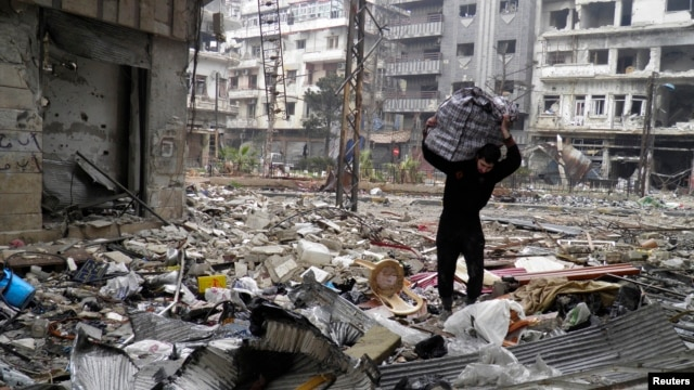 A man carries a bag amid damage and debris in the besieged area of Homs, Jan. 26, 2014.