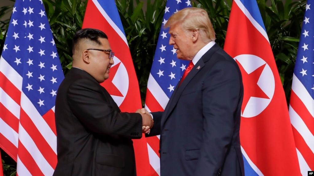 도널드 트럼프 미국 대통령과 김정은 북한 국무위원장이 12일 싱가포르 카펠라 호텔에서 역사적인 첫 미북 정상회담에 앞서 악수하고 있다.