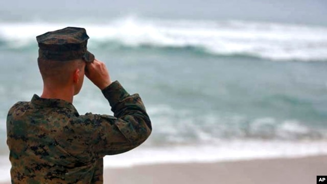 A U.S. Marine Corps officer uses binoculars to search for debris of two helicopters missing off the coast of Hawaii, in Haliewa Beach Park, Hawaii, Jan. 15, 2016.