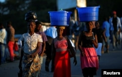 Women carry baskets with food items on their heads at a market in Blantyre, Malawi, July 10, 2017.