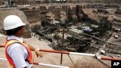 老挝一名工人在调查一座大坝的建筑情况(资料照)