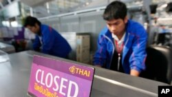 FILE - Airport staff inspect the ticketing counter at the Suvarnabhumi Airport in Bangkok.
