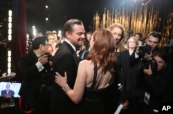 "Leonardo DiCaprio, winner of the award for best actor in a leading role for ""The Revenant"" (l) and Julianne Moore appear backstage at the Oscars, Feb. 28, 2016, at the Dolby Theatre in Los Angeles."