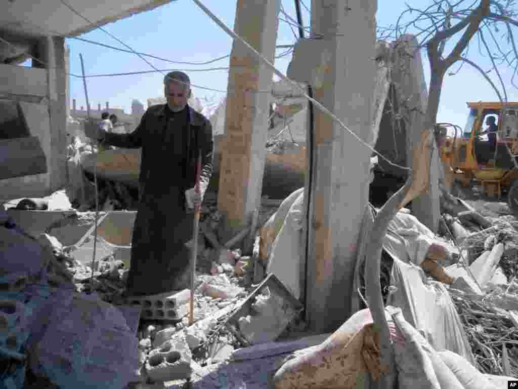 Hava hücumu nəticəsində evi dağılmış Quseyr sakini.
