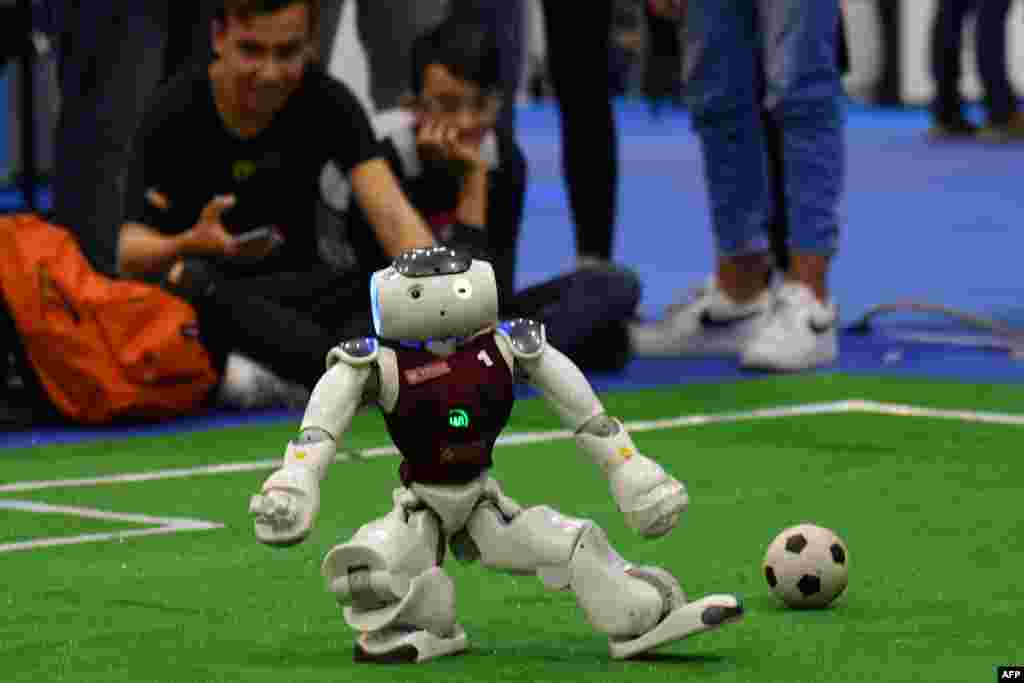 Visitors watch a competition of robot soccer players at the 7th edition of the Maker Faire 2019, a huge European event on innovation, in Rome.