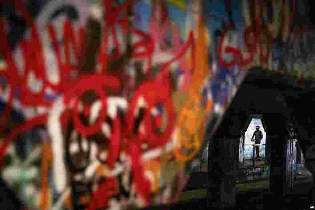 A person rides a scooter through Atlanta's Krog Street Tunnel, which runs under train tracks carrying freight cars and is known for its urban street art, Atlanta, Georgia.
