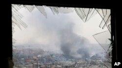 une fenêtre brisée par les ondes de choc encadrent le site d'une explosion dans un entrepôt dans la municipalité de Tianjin au nord-est de la Chine , le 14 Août 2015.