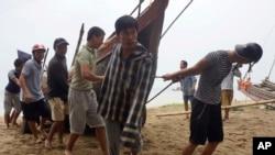 Dân làng tìm cách lôi tàu cá lên bờ ở tỉnh Thanh Hóa, Vietnam, hôm 14/9/2017. Bão Doksuri tuần trước hoành hành tại các vùng biển miền Trung được coi là bão nhiệt đới mạnh nhất từng ập vào Việt Nam trong nhiều năm qua.