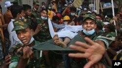25일 방글라데시 다카 외곽에서 발생한 건물 붕괴 사고 현장에서 한 생존자를 구출하는 구조대원들.