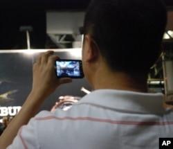 大陸遊客孟先生用手機拍攝六四報哀音的演出情況