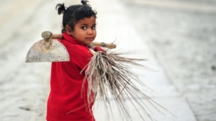 FILE - Young Indian child Laxmi carries a broom and hoe as she walks with her mother after working at the site of the annual traditional fair Magh Mela at Sangam, the confluence of the rivers Ganges and Yamuna, and the mythical Saraswati in Allahabad on January 2, 2015.