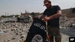 Солдат сирійської християнської міліції із здобутим прапором «Ісламської держави»