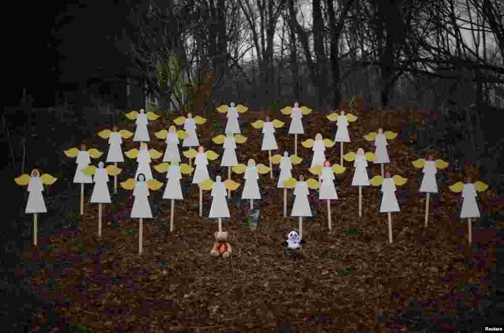 27个木制天使竖立在康州纽顿桑迪胡克小学附近路上的树林里。(2012年12月16日)