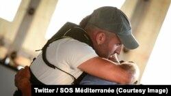 Un membre des équipes de l'ONG SOS Méditerranée embrasse un des cinq migrants après la décision de ceux-ci de repartir en Tunisie, à bord du navire humanitaire Aquarius, sur la Méditerranée, 25 août 2018. (Twitter/ SOS Méditerranée)
