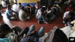 Would-be illegal asylum seekers from Sri Lanka are seen at a police station in Colombo after attempting to sail to Australia illegally by boat, May 28, 2012.