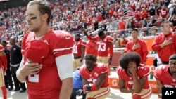 FILE - San Francisco 49ers quarterback Blaine Gabbert, left, stands as Eli Harold, from bottom left, Colin Kaepernick and Eric Reid kneel during the national anthem before an NFL football game in Santa Clara, California, Oct. 2, 2016.