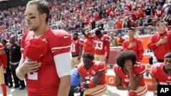 FILE - San Francisco 49ers quarterback Blaine Gabbert, left, stands as Eli Harold, from bottom left, Colin Kaepernick and Eric Reid kneel during the national anthem before an NFL football game in Santa Clara, California, Oct. 2, 2016.