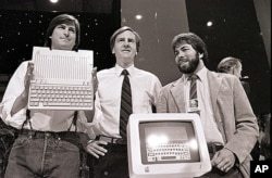 FILE - Steve Jobs, left, John Sculley, center, president and CEO of Apple, and Steve Wozniak, co-founder of Apple, unveil the new Apple II computer in San Francisco on April 4, 1984.