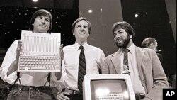Steve Jobs (kiri), John Sculley (tengah), presiden dan CEO Apple, serta Steve Wozniak, salah satu pendiri Apple, memperlihatkan komputer Apple II di San Francisco pada 4 April 1984. (AP)