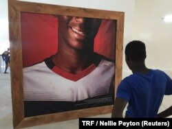 "A teenager looks at his photograph displayed at the ""Look at me"" exhibition, Dakar, Senegal, May 11, 2018."