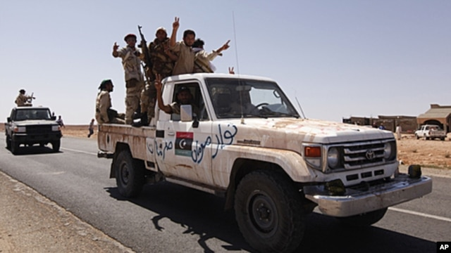 Anti-Gaddafi fighters travel on a vehicle at a strategic checkpoint, after returning from the north of the besieged city of Bani Walid, Libya, September 23, 2011.