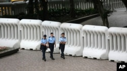 Police officers patrol in front of crowd-control barriers near the hotel where top Chinese official, Zhang Dejiang, will stay during his three-day visit to Hong Kong, May 17, 2016. The semiautonomous city has been the scene of rising discontent with Chinese rule.