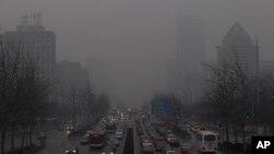 Antrian panjang kendaraan terlihat di jalanan Beijing diantara gedung-gedung pencakar langit yang tertutup asap polusi (Foto: dok). Sebagian ilmuwan mengatakan kegiatan manusia dan polusi dari mobil dan pabrik juga ikut berperan dalam memanasnya suhu Bumi.