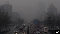 擁擠在霧霾籠罩下的北京一條要道上爬行的車輛(2013年1月31日照片)