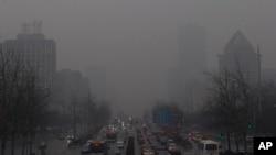 拥挤在雾霾笼罩下的北京一条要道上爬行的车辆(2013年1月31日照片)