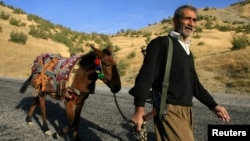 FILE - A Kurdish village guard patrols a road in the southeastern Turkish province of Sirnak. A Turkish pro-Kurdish lawmaker accused the military of slaughtering many mules after raking a village with gunfire in the Uludere district.