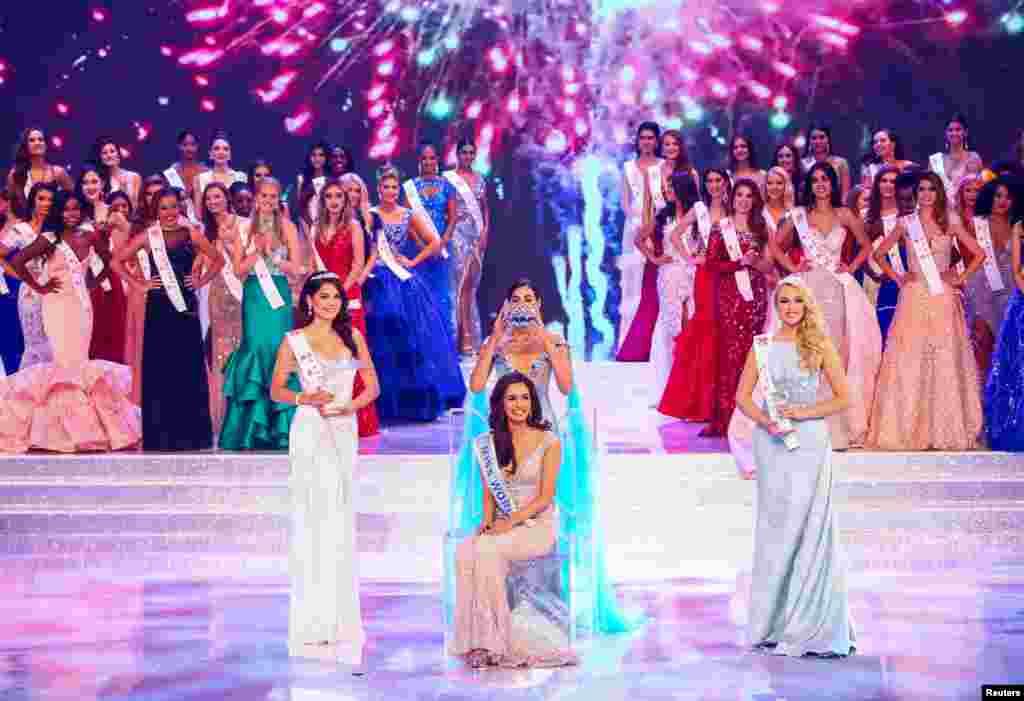 """在中国海南省三亚市举行的世界小姐选美赛中,前任世界小姐为新科世界小姐齐希拉加冕。第67届世界小姐全球总决赛在中国海南三亚举行,来自126个国家和地区的126名佳丽参赛。中国小姐入围前40名,澳门小姐进入全球15强(2017年11月18日)。这是三亚第七次举行世界小姐决赛。中国从早年的排斥选美""""和平演变""""到变相选美再到拥抱选美,三亚以优厚条件争取成为决赛地点。"""