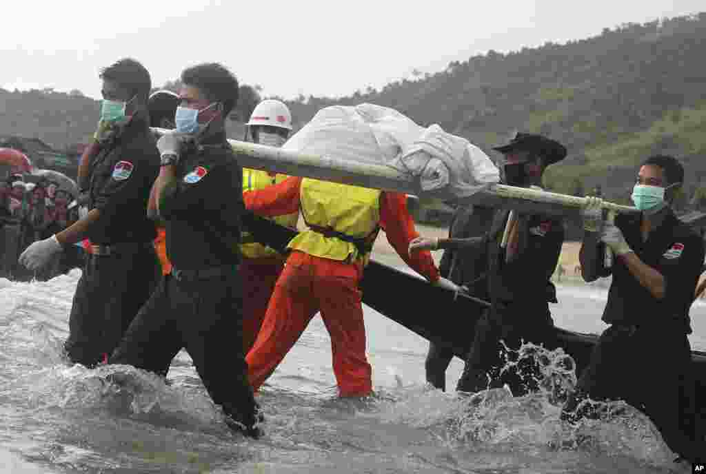 Rescue personnel carry bodies recovered by fishing vessels in the waters off San Hlan village, in Laung Lone township, southern Myanmar. Fishermen have joined navy and air force personnel in recovering bodies and aircraft parts from the sea off Myanmar, where a military plane carrying 122 people including 15 children crashed a day earlier.