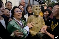 """ອະດີດ """"ຄອມຟອຣ໌ດ ວູເມນ (comfort woman)"""" ຢັງຊູ ລີ (Yongsoo Lee) 89, ຂອງເກົາຫຼີໃຕ້, ຢືນຢູ່ຂ້າງຮູບປັ້ນຂອງທ່ານຮັກຊຸນ ກິມ (Haksoon Kim) ໃນຂະນະທີ່ເບິ່ງ """"Comfort Women"""" ບໍ່ເທົ່າໃດນາທີ, 22 ກັນຍາ 2017, ໃນຊານຟຣານ ຊິສໂກ."""