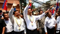 Cambodia's opposition leader Sam Rainsy, center, of the Cambodia National Rescue Party waves along with his party Vice President Kem Sokha, third from left, during a march in Phnom Penh, file photo.