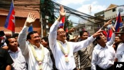 Cambodia's opposition leader Sam Rainsy, center, of the Cambodia National Rescue Party waves along with his party Vice President Kem Sokha, third from left, during a march in Phnom Penh, Cambodia, Sunday, March 30, 2014.