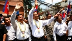 FILE PHOTO - Cambodia's opposition leader Sam Rainsy, center, of the Cambodia National Rescue Party waves along with his party Vice President Kem Sokha, third from left, during a march in Phnom Penh, Cambodia, Sunday, March 30, 2014.