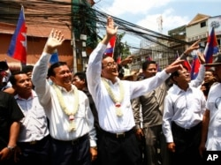 FILE - Cambodia's opposition leader Sam Rainsy, center, of the Cambodia National Rescue Party waves along with his party Vice President Kem Sokha, third from left, during a march in Phnom Penh, Cambodia, Sunday, March 30, 2014.