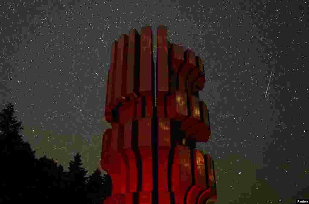 A meteor streaks across the sky near the Monument to the Revolution at Kozara during the peak of the Perseid meteor shower in Prijedor, Bosnia and Herzegovina.