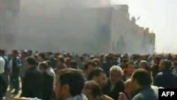 Một đám đông tụ họp gần 1 tòa nhà đang bốc khói ở thành phố Benghazi, 20/2/2011