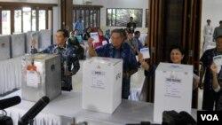 Presiden Susilo Bambang Yudhoyono, Ibu Negara Ani Yudhoyono dan putra bungsu mereka Edhie Baskoro Yudhoyono memasukkan kertas suara ke kotak suara. (VOA/Andylala Waluyo)