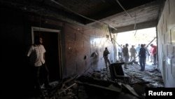 Security personnel inspect damage in the Swedish consulate after a car bomb exploded at its entrance, in Benghazi, Oct. 11, 2013.
