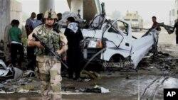 Pasukan keamanan Irak dan warga setempat memeriksa lokasi serangan bom mobil di distrik Husseiniyah, pinggiran Baghdad, Senin (6/5).