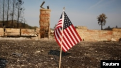 FILE - An American flag stands in front of a home destroyed after a wildfire tore through Santa Rosa, California, Oct. 15, 2017.