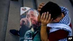 Seorang mahasiswa kedokteran Palestina, Adham Motawi, membawa gambar Fidel Castro, berduka atas kematiannya dalam sebuah acara memorial di Havana, Kuba, sehari setelah kematiannya (26/11). (AP/Ramon Espinosa)