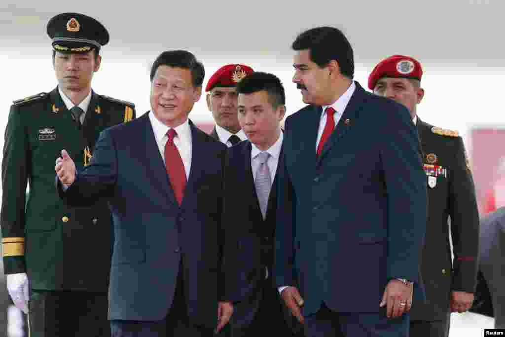 Chinese President Xi Jinping, second from left, gestures as he is welcomed by his Venezuelan counterpart Nicolas Maduro at the Simon Bolivar airport, in Caracas, July 20, 2014.