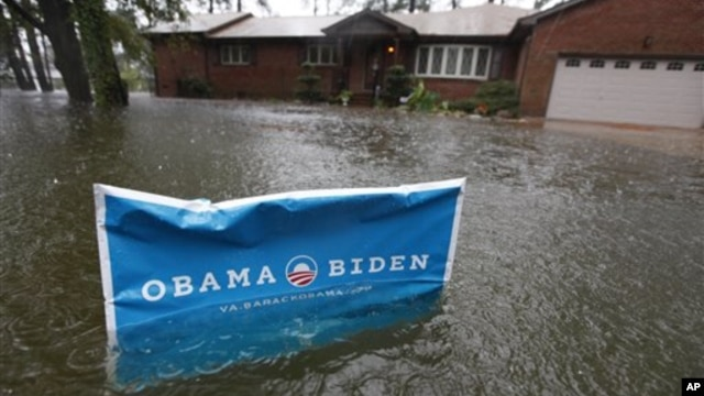 A campaign sign rises above floodwaters as rain continues falling in Norfolk, VA, Oct. 29, 2012.
