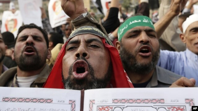Supporters of President Mohamed Morsi chant slogans holding the Quran ahead of Egypt's controversial constitutional referendum, Cairo, December 14, 2012.