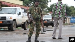 FILE - A Burundian soldier with his gun and rocket launcher guard a deserted street in Bujumbura, Burundi.
